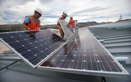 Workers Attaching Solar Panels to Roof Racking